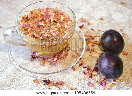drink of tea rose petals, transparent cup and saucer, plums