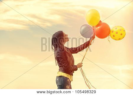smiling young woman in blue jeans and leather jacket  with balloons outdoors, side view, retro colors