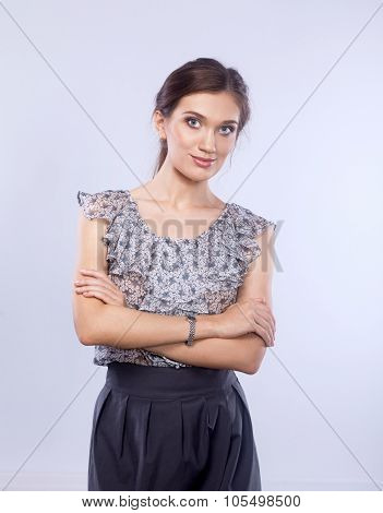 Full-body portrait of a happy business woman looking at camera with arms folded. Isolated on white b