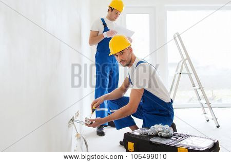 building, renovation, technology, electricity and people concept - two builders with tablet pc computer working with electricity indoors