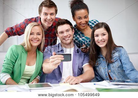 education, people, friendship, technology and learning concept - group of happy international high school students or classmates with smartphone taking selfie in classroom