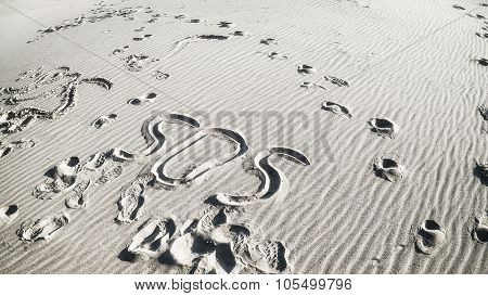 Inscription Sos And Footprints In The Sand