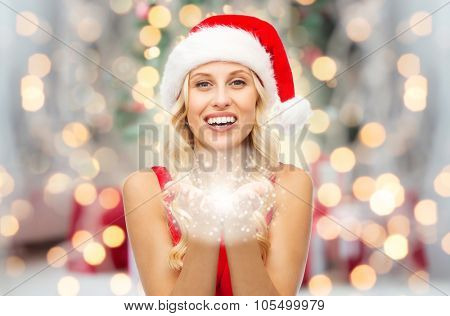 people, holidays, christmas and magic concept - happy blonde woman in santa hat holding fairy dust on palms over lights background