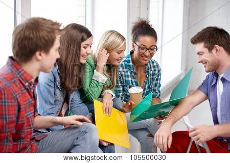 education, people, friendship and learning concept - group of happy international high school students or classmates with folders