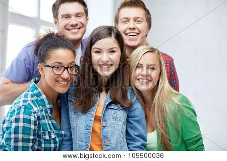 education, people, friendship and learning concept - group of happy international high school students or classmates
