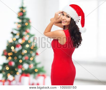 people, holidays, christmas and celebration concept - beautiful sexy woman in santa hat and red dress over room with christmas tree and gifts background