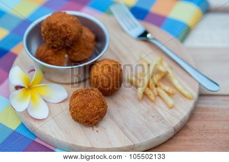 Deep Fried Cheese Ball And French Fries On Wood Dish