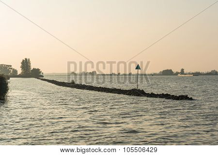 Breakwater In A Wide River In Evening Light