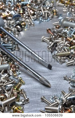 Screwdrivers and hardware bolts nuts washers screws on metal surface