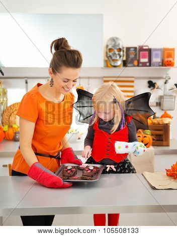 Halloween Dressed Girl With Mother Holding Tray With Biscuits