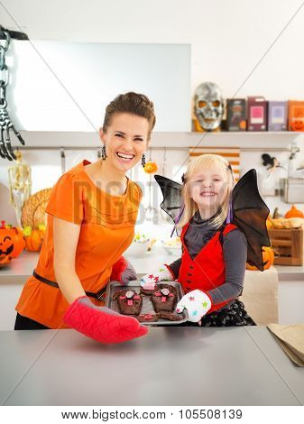 Girl With Mother Holding Tray With Halloween Cookies In Kitchen
