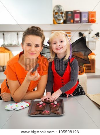 Portrait Of Mother And Girl With Baked Halloween Biscuits
