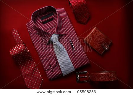 Red dress shirt and leather background with ties, wallet and belt