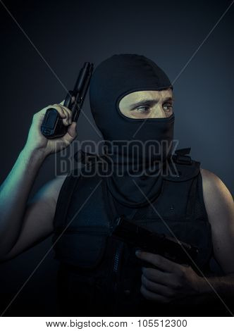 Gangster, terrorist carrying a machine gun and balaclava
