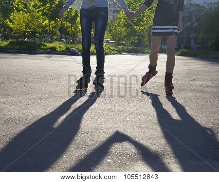 Female roller skaters holding hands