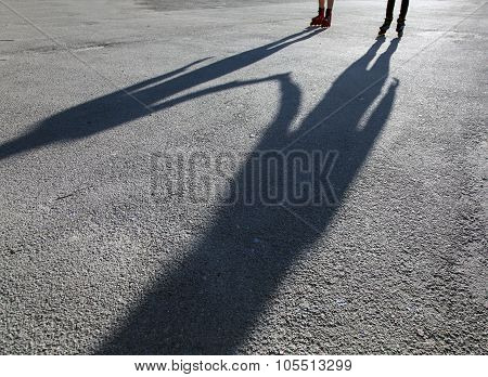 Shadows of skaters on asphalt