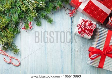 Christmas gift boxes and fir tree branch on wooden table. Top view with copy space