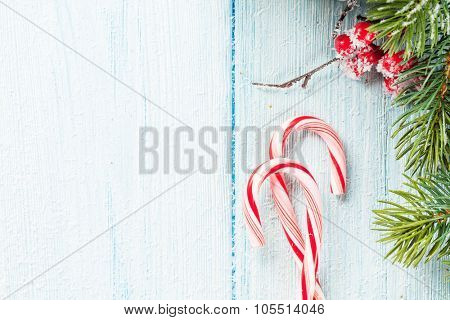 Candy cane and christmas tree on wooden table. Top view with copy space