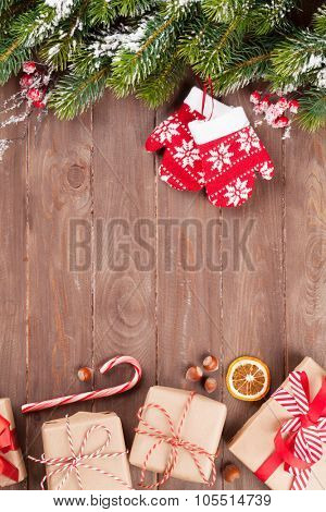 Christmas wooden background with snow fir tree and gift boxes. View with copy space