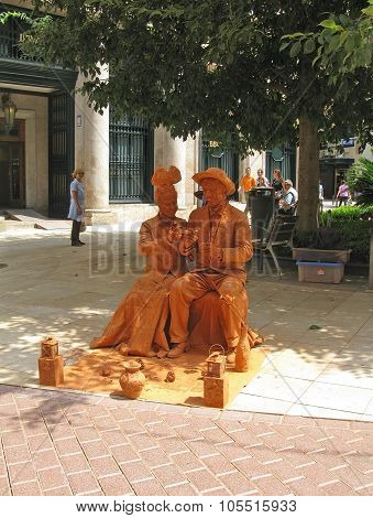 Two mime artists covered in red clay
