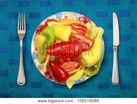 bell peppers on plate, knife and fork on table