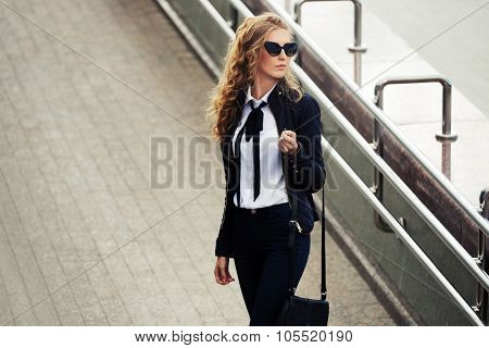 Young fashion business woman in sunglasses walking on the city street