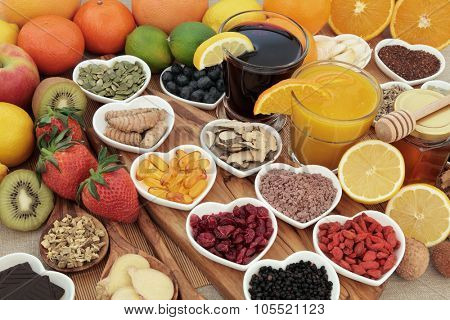 Super food selection for cold and flu remedy including foods high in vitamin c and antioxidants with herbal medicine and supplement capsules.