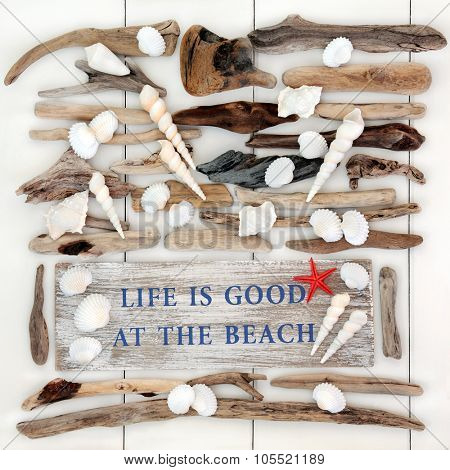 Abstract background with life is good at the beach sign with driftwood and seashells on white wood.