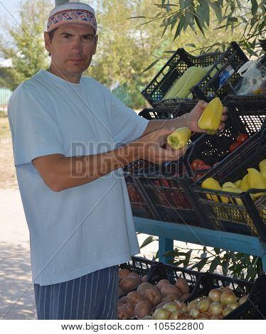 a man selling vegetables and fruits in summer