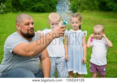 Father shoots of the firecracker with confetti on a family holiday.
