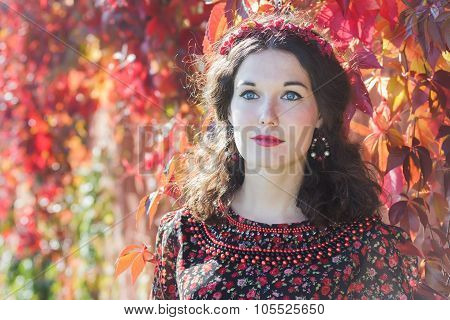Portrait of fairy autumn girl with red fall wreath at red floral background of Virginia creeper