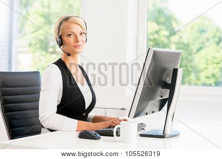 Beautiful woman in headset working in call center.
