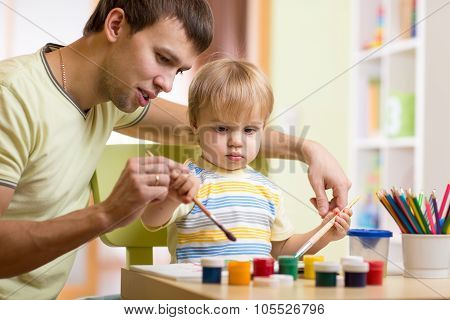 child boy painting in nursery at home
