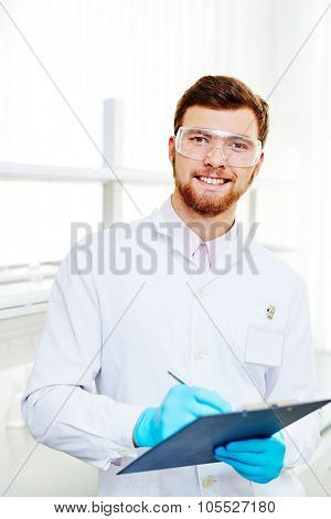 Handsome chemist in white-coat, eyeglasses and gloves making notes in lab