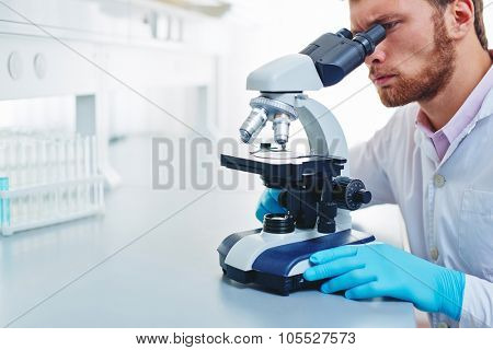 Young man studying new microbiological substance in microscope