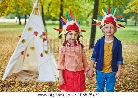 Little girl and boy in Indian headdresses looking at camera in autumn park