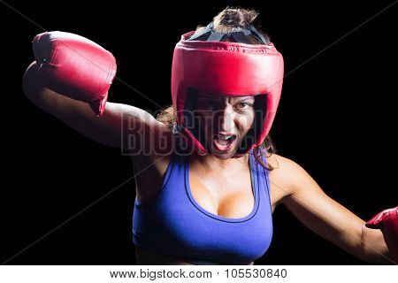 Portrait of angry female boxer with fighting stance against black background