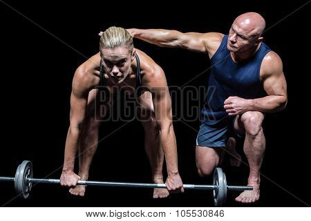 Trainer by woman for lifting crossfit against black background