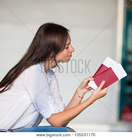 Happy woman with air ticket and passports at airport waiting for boarding