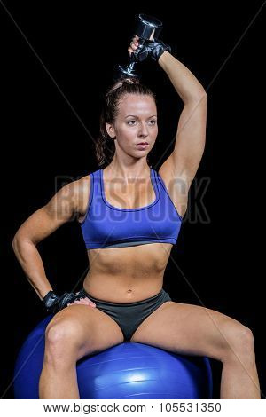 Woman exercising with dumbbell while sitting on ball against black background