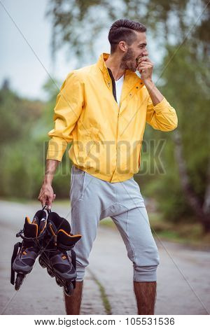 Handsome man holding inline skates in the countryside