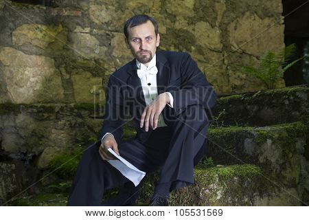Portrait Of Man In Dress Coat Sitting On Steps With Letter In His Hands.