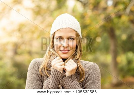 Portrait of smiling woman holding her scarf on an autumns day