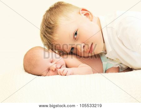 Two Children Lying On Bed, Eldest Brother Hugging Youngest Baby