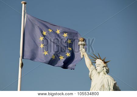 European Union Flags  And Statue Of Liberty, Under Blue Sky Background. Alliance. Blue Sky Backgroun