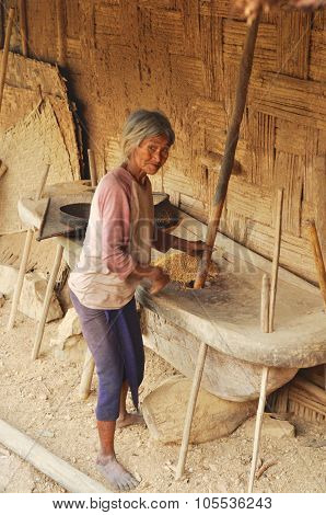 Old Woman Grinding Grain In Nagaland, India