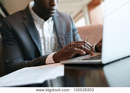 African Businessman Working On Laptop At Cafe