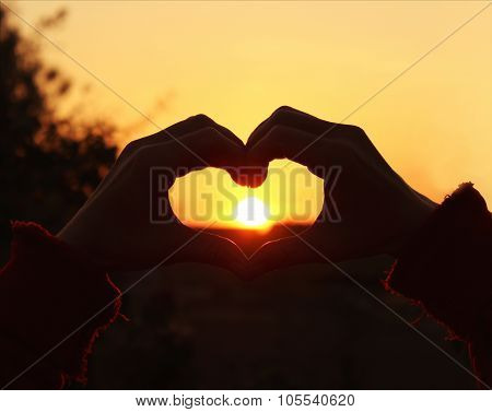 Women's hands are crossed in the form of the heart through which the sun's rays make the way at the
