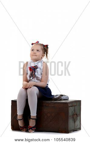beautiful young female child model sitting on a chest on white background