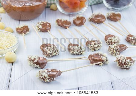 Making Apricot And Prunes Lollipops, Covered With Chocolate And Macadamia Nuts